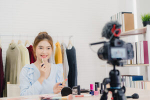 Beauty blogger present beauty cosmetics while sitting in front c